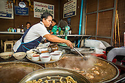 16 FEBRUARY 2013 - BANGKOK, THAILAND:     A soup vendor prepares an order for customers in Chatuchak Weekend Market in Bangkok. It is reportedly the largest market in Thailand and the world's largest weekend market. Frequently called J.J., it covers more than 35 acres and contains upwards of 5,000 stalls.       PHOTO BY JACK KURTZ