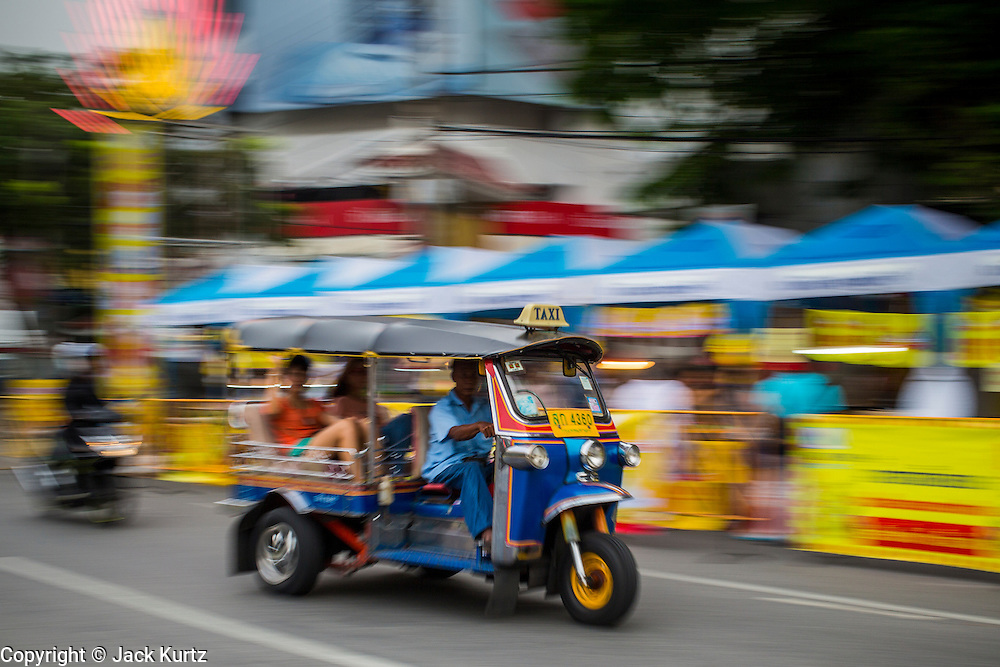 """17 OCTOBER 2012 - BANGKOK, THAILAND:      A """"tuk-tuk,"""" or three wheeled taxi, on Yaowarat Road during the Vegetarian Festival in Bangkok's Chinatown. The Vegetarian Festival is celebrated throughout Thailand. It is the Thai version of the The Nine Emperor Gods Festival, a nine-day Taoist celebration celebrated in the 9th lunar month of the Chinese calendar. For nine days, those who are participating in the festival dress all in white and abstain from eating meat, poultry, seafood, and dairy products. Vendors and proprietors of restaurants indicate that vegetarian food is for sale at their establishments by putting a yellow flag out with Thai characters for meatless written on it in red.       PHOTO BY JACK KURTZ"""