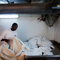 "Ali a sudanese refugee separates towels from sheets as he works in the laundry of the Royal Beach Hotel on February 28 2011. The municipality hung 1,500 red flags around the city as a sign of warning and put up hundreds of banners reading: ""Protecting our home, the residents of Eilat are drawing the line on infiltration."" Eilat Mayor Meir Yitzhak Halevi said that 10 percent of the city's population was currently made up of migrants and that the residents feel that the city has been conquered...Photo by Olivier Fitoussi."