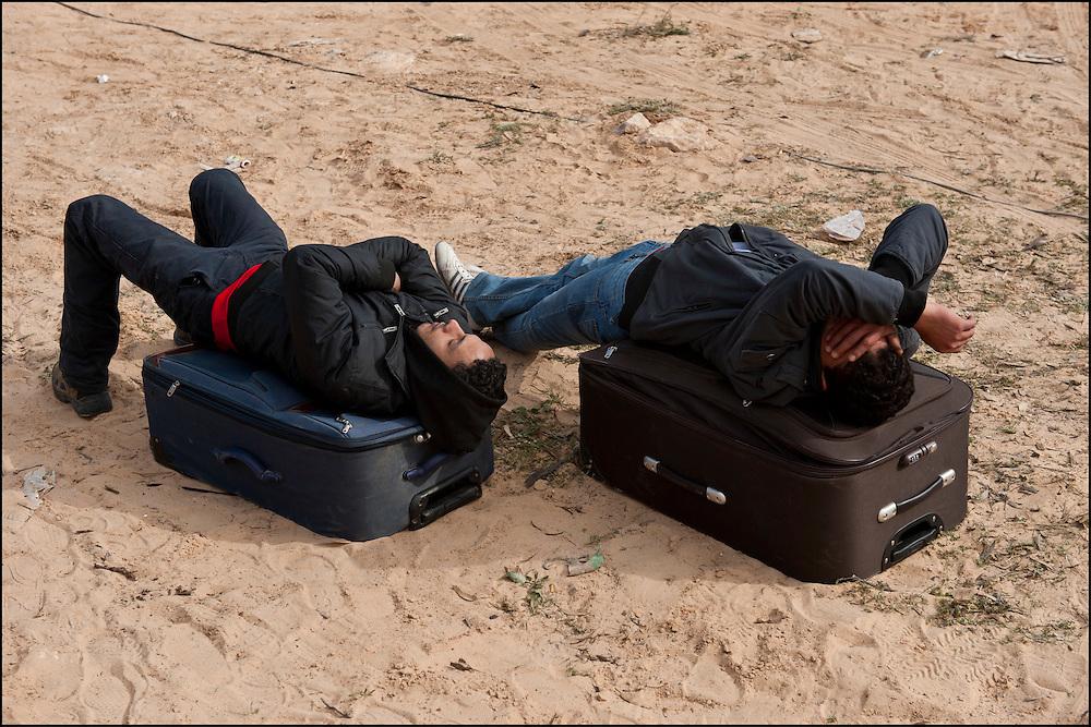 Des réfugiés se reposent à leur arrivée au camp humanitaire Choucha à 8km de la frontière. Plus de 140 000 réfugiés ont déjà quitté la Libye par la Tunisie ou l'Egypte et des milliers continuent d'arriver chaque jours. Vendredi 25 février 2011, Camp Choucha, Tunisie..© Benjamin Girette/IP3 press