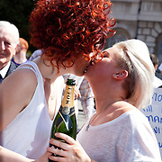 The moment when it is announced that the Same Sex Marriage bill had been passed. London Gay Chorus and supporters of the bill celebrate outside the House of Lords. A lesbian couple kiss and drink champaign. The campaign for the bill has lasted decades. Summary of the Marriage (Same Sex Couples) Bill 2012-13 to 2013-14<br /> A Bill to make provision for the marriage of same sex couples in England and Wales, about gender change by married persons and civil partners, about consular functions in relation to marriage, for the marriage of armed forces personnel overseas, and for connected purposes.