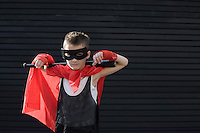 Boy wearing Zorro costume with baseball bat