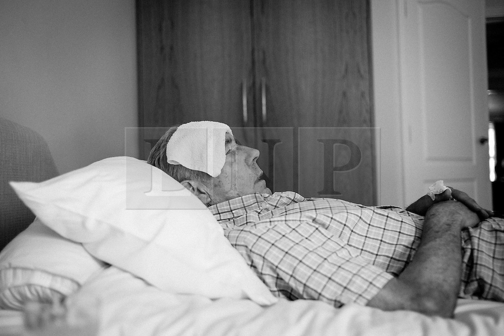 © Licensed to London News Pictures. 09/04/2014<br /> These photographs have been converted to black and white<br /> <br /> Durham, United Kingdom<br /> <br /> Parkinson's Disease sufferer David Forsyth from Brandon, County Durham lies on his bed with a cold cloth on his forehead to try and reduce a fever during a respite stay in a care home.<br /> <br /> These visits to a care home are becoming more frequent as the demands on him and his wife who provides full time care to him begins to take a toll.<br /> <br /> Parkinson's is a long-term neurological condition that affects the way the brain co-ordinates body movements including walking, talking and writing and affects both men and women.<br /> <br /> Photo credit : Ian Forsyth/LNP