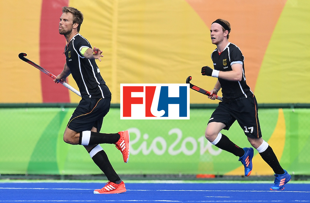 Germany's Moritz Furste (L) celebrates scoring a goal with teammates during the men's field hockey Germany vs Ireland match of the Rio 2016 Olympics Games at the Olympic Hockey Centre in Rio de Janeiro on August, 9 2016. / AFP / MANAN VATSYAYANA        (Photo credit should read MANAN VATSYAYANA/AFP/Getty Images)