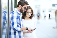 Smiling couple using smart phone together in city