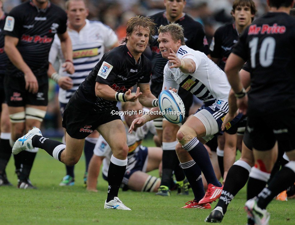 Sharks scrumhalf Charl McLeod passes the ball with Stormers centre Jean de Villiers looking on during a Super 15 rugby match in Durban, 2 April , 2011. Sportzpics