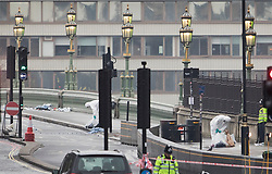 © Licensed to London News Pictures.23/03/2017.London, UK. Forensics officers are seen collecting evidence in bags on Westminster Bridge near Parliament, the day after a lone terrorist killed 4 people and injured several more, in an attack using a car and a knife. The attacker managed to gain entry to the grounds of the Houses of Parliament, killing one police officer.Photo credit: Peter Macdiarmid/LNP