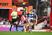 Queens Park Rangers Defender Jake Bidwell (3) comes in for a strong challenge against Brentford Forward Neal Maupay (9) earning himself a yellow card during the EFL Sky Bet Championship match between Brentford and Queens Park Rangers at Griffin Park, London, England on 21 April 2018. Picture by Stephen Wright.