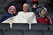 A family huddle up under a blanket during the EFL Sky Bet League 2 match between Milton Keynes Dons and Mansfield Town at stadium:mk, Milton Keynes, England on 4 May 2019.