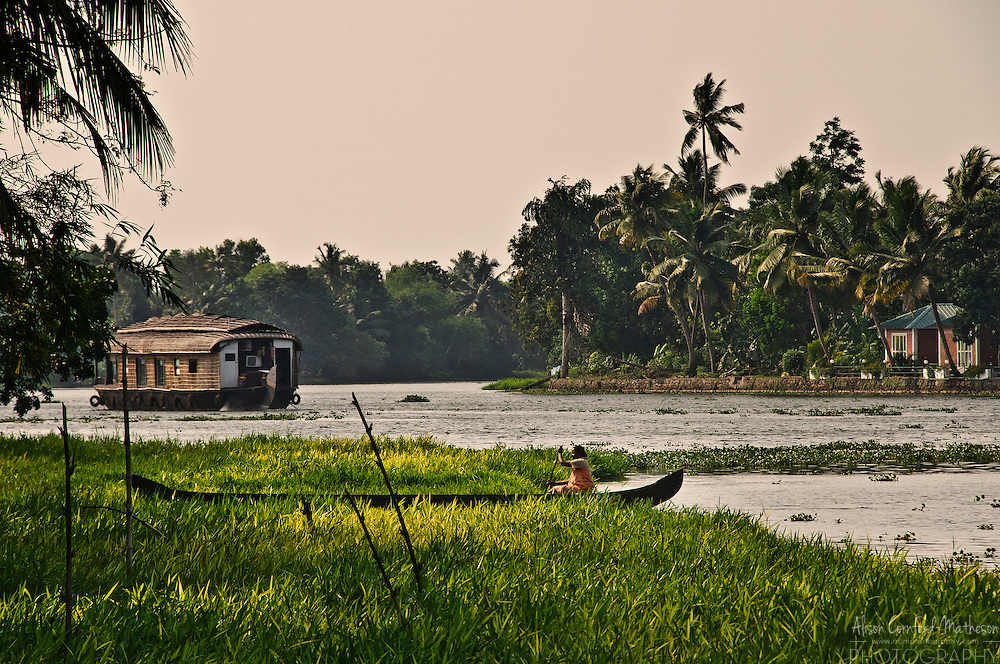 A woman navigates a boat on the Kerala Backwaters with a traditional houseboat in the background