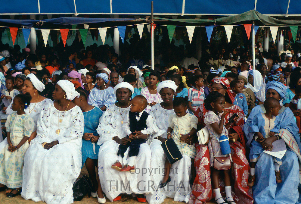 Gambians smartly dressed sitting with their children while watching an Independence Day parade in Banjul, The Gambia, West Africa.