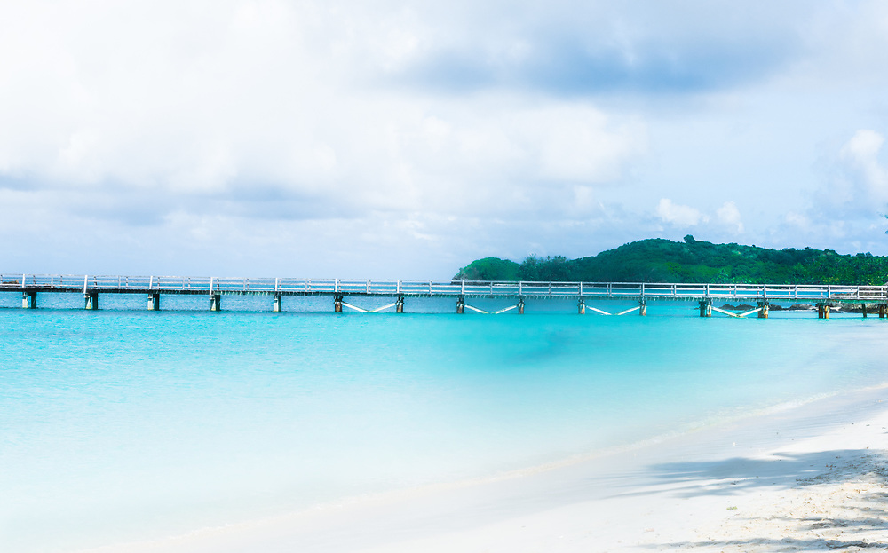 Dreamy photo of a dock stretching out into the Pacific Ocean from  a Yasawa-I-Rara beach.