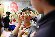 Brandon Chiang, 6, places sliced cucumbers over his mother's, Wen Tseng, eyes during the 1st grade Mother's Day Spa Day at Sinnott Elementary School in Milpitas, California, on May 10, 2013. (Stan Olszewski/SOSKIphoto)