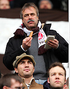 Heavyweight Champion Wladimir Klitschko watches FC St Pauli from the stands whilst his manager eats a hotdog. Hamburg, Germany, 8th Feb 2009.