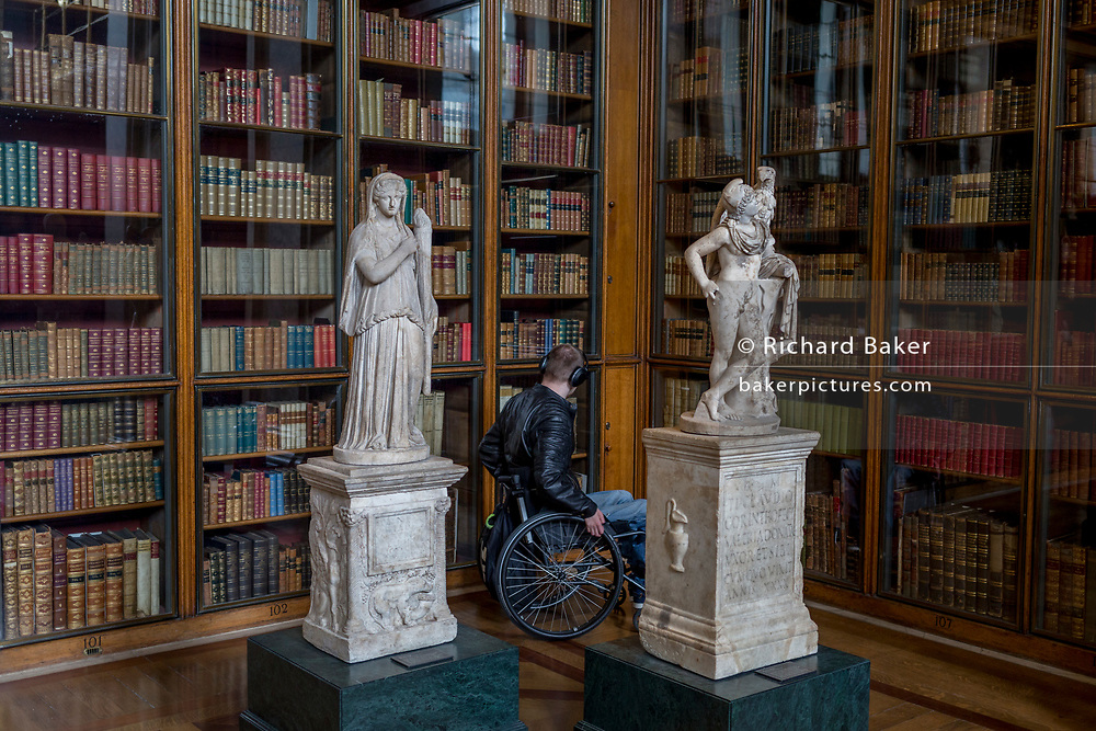 A wheelchair user is between 2nd century Roman copies from Greek originals of Demeter holding a torch (L) and Gannymede with the eagle of Zeus (R), in the Enlightenment Gallery of the British Museum, on 11th April 2018, in London, England.