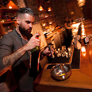 """November 18, 2013 - New York, NY : Bartender Maks Pazuniak adds Cynar as he makes his winter-warming cocktail, the """"Bitter Coffee,"""" at The Counting Room on Berry Street in Williamsburg in Brooklyn on Monday evening. The drink is comprised of Cynar, dark rum, maple syrup, an egg yolk, vanilla, coffee, and a grating of nutmeg.  CREDIT: Karsten Moran for The New York Times  CREDIT: Karsten Moran for The New York Times"""