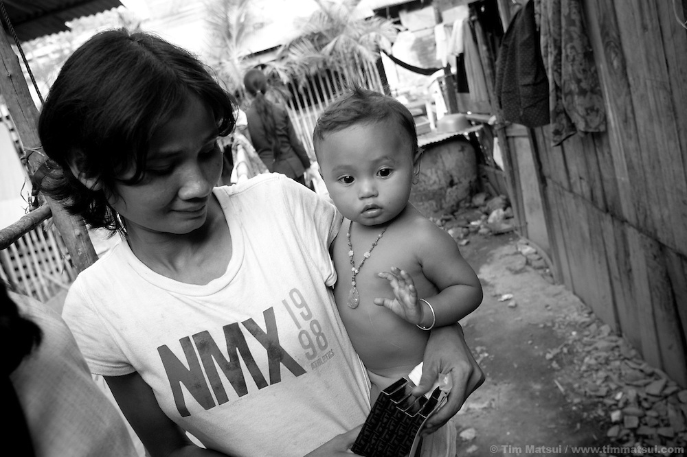 """A young woman in a slum receives condom from a social worker with the agency """"Acting for Women in Distressing Situations"""" (AFESIP) which conducts outreach and provides services in Phnom Penh, Cambodia. The permanent structure, a decaying four story building known simply as 'The Building', was built in the 1960's as transitional housing and now hosts a shantytown where many of the city's poor live, including many prostitutes, and is believed to have the highest rate of HIV infection in the city. AFESIP hands out free condoms, instructs prostitutes on HIV prevention, and conducts outreach in case the prostitutes need medical services, choose to leave their profession, or can report on cases of sex trafficking. AFESIP offers housing, education, training, and counseling for women who are victims of sex trafficking, worked as prostitutes, or are escaping domestic violence. Founded by Somaly Mam, who herself was once a prostitute and victim of trafficking and domestic abuse, AFESIP has three facilities in Cambodia and works with other NGO's to provide long term care for the women."""