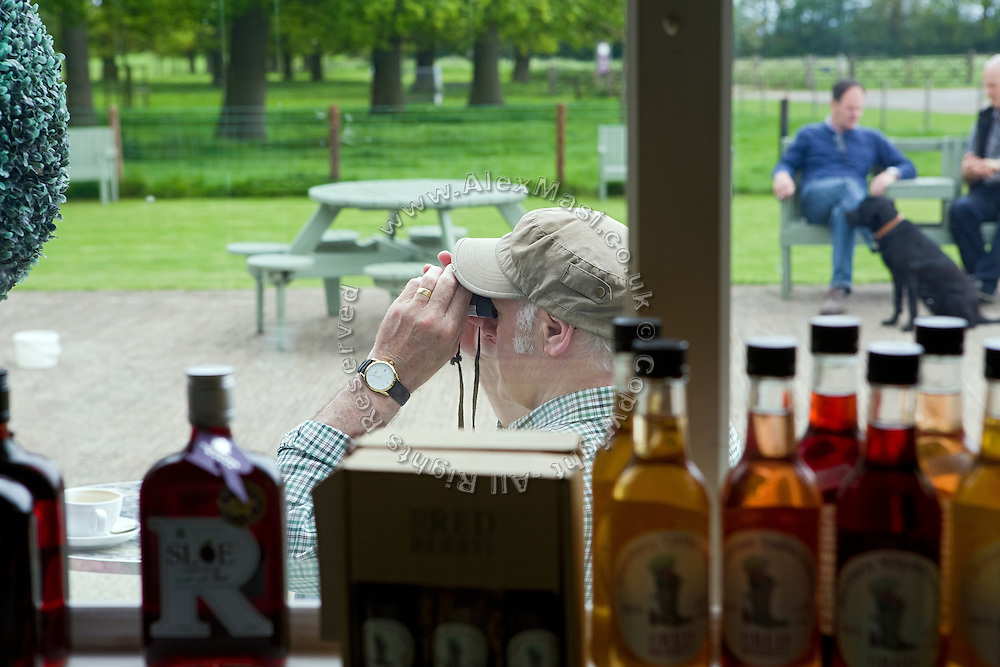 A tourist is using a binocular while sitting at a traditional shop in Beningbrough, Yorkshire, England, United Kingdom.