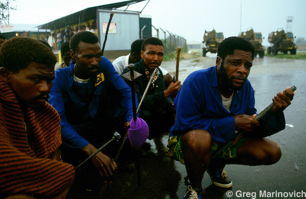 Ratanda township, Heidelberg, Transvaal, South Africa, 1992. Xhosa ANC supporting warriors wait in a thunderstorm as they prepare to attack IFP supporters during clashes between ANC supporting residents and Inkatha Freedom party supporters from the hostel.