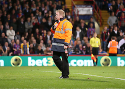 A security guard clears Coke bottles thrown on by Crystal Palace supporters unhappy at Referee Lee Mason - Photo mandatory by-line: Robin White/JMP - Tel: Mobile: 07966 386802 21/10/2013 - SPORT - FOOTBALL - Selhurst Park - London - Crystal Palace V Fulham - Barclays Premier League