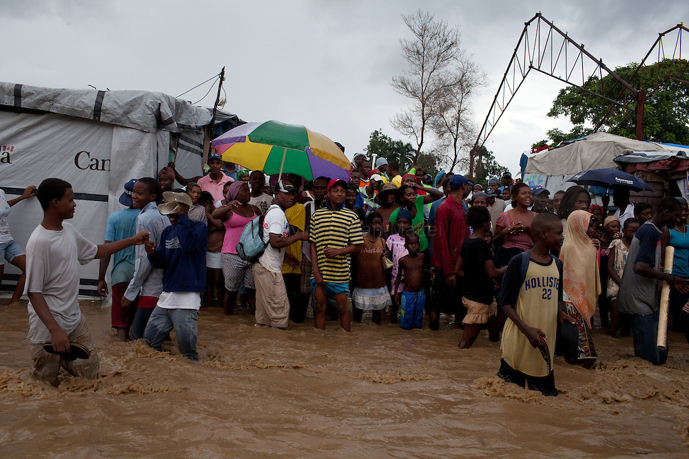 After hurricane Tomas went through Haiti, the city of Leogane has been totally flooded by the heavy rain and the overflow of the river Roullorne.///Haitian refugees stand before their tents, in a street of Leogane full of muddy water, during hurricane Tomas.