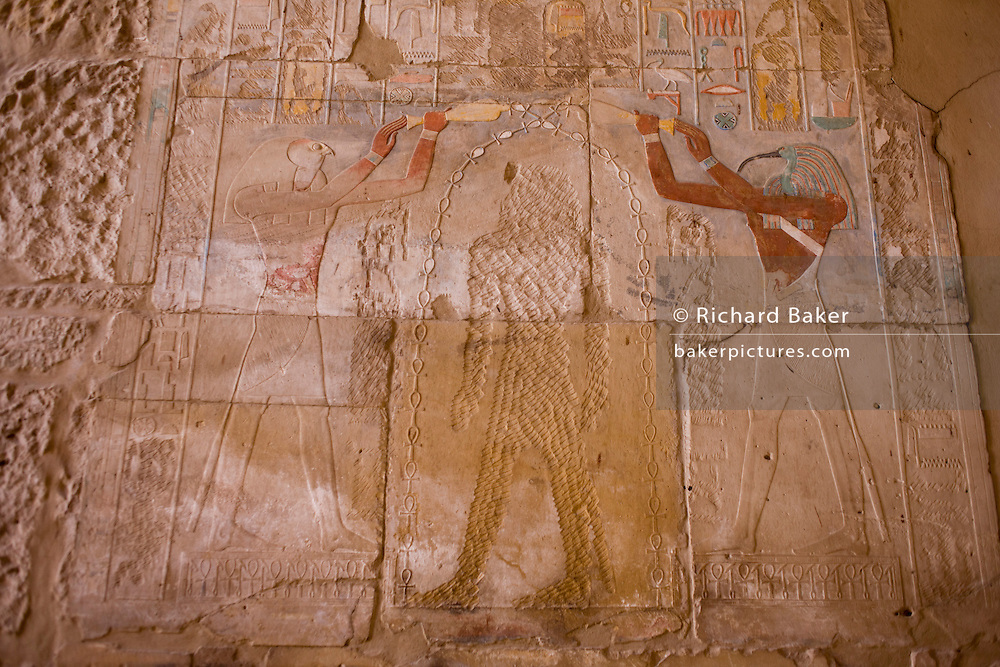 A detail of a defaced Queen Hatshepsut in temple of Amun at Karnak at the Temple of Amun at Karnak, Luxor, Nile Valley, Egypt. Queen Hatshepsut reigned from 1473 to 1458 BC but her successor Tuthmosis III quashed an Asiatic uprising and records of Hatshepsut disappeared. Tuthmosis III was finally able to claim his rightful place as King of Egypt and all images of Hatshepsut were attacked; statues, reliefs and shrines all were defaced. While the queen was damaged, the Gods either side in this painting were left untouched. The Karnak Temple Complex is the largest religious building ever made, covering about 200 acres. It comprises a vast mix of decayed temples, chapels, pylons, and other buildings built over 2,000 years and dedicated to the Theban triad of Amun, Mut, and Khonsu.