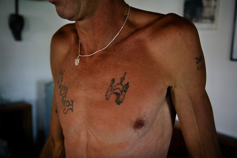 "Adem Mocca Pajevic, 50, recently returned to Mostar after 14 years living in Kentucky, USA. He is a war veteran and a professional diving coach who first leapt from the Old Bridge in 1975. He now spends his days as a Mostari in his hometown. The tattoos on his chest read ""Kentucky Diving Frog"" and an image of the Old Bridge and a Mosque...Divers and tourists at Mostar's famous Old Bridge (Stari Most) in Bosnia and Herzegovina. This bridge is the city and region's biggest tourist attraction and there are busses full of tourists coming in from Sarajevo and Dubrovnik, Croatia. For 25euros tourists can train to jump from the bridge themselves, under supervision from the ""professional"" Mostar divers known as the Mostari. .."