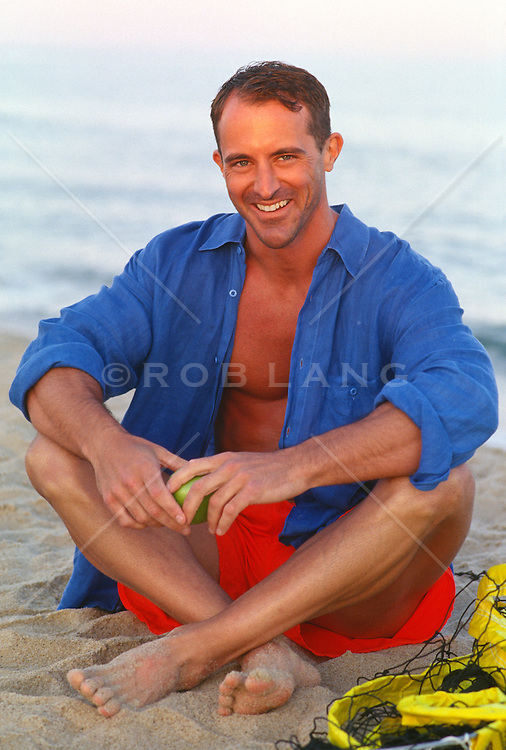 Man sitting on the beach with red shorts and an open blue button up shirt smiling at camera