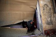 A female shop owner climbs out of her shop looted by syrian troops. On 22. February the syrian army attacked the village of Kureen, Province of Idlib, Syria. Kureen was among the first villages in the northwest of Syria controlled by the opposition. Some villagers and members of the defence units escaped to surrounding olive orchards, when the attack begun in the early morning. A majority of the inhabitants didn´t manage to escape. The heavy shelling lasts 7 houres. Soldiers searched all houses, burnt some of them down, loote shops, stole cars and furniture. About 60 motorcycles were burnt down. Tanks demolished several houses. 6 men were executed. One woman died as a result of an heart attack.