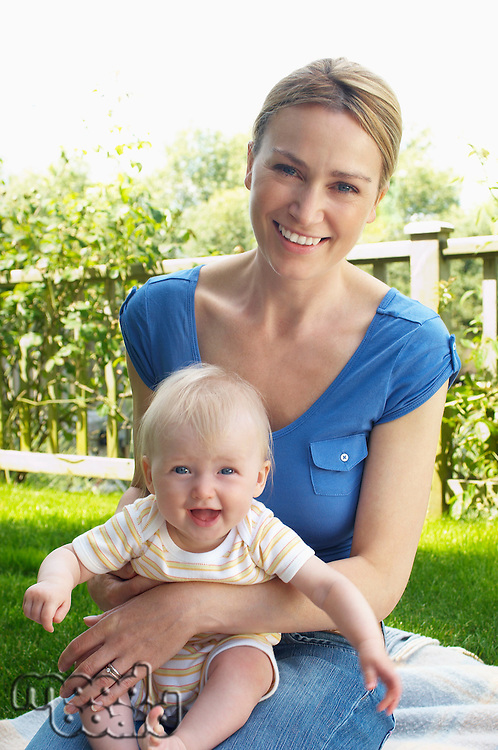 Mother and son sitting on rug in garden