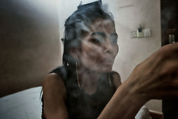 A prostitute is smoking Ice in a hotel room, Phnom Penh, Cambodia. <br />