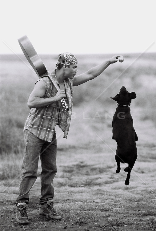 Young man holding guitar and ball, playing with dog (B&W)