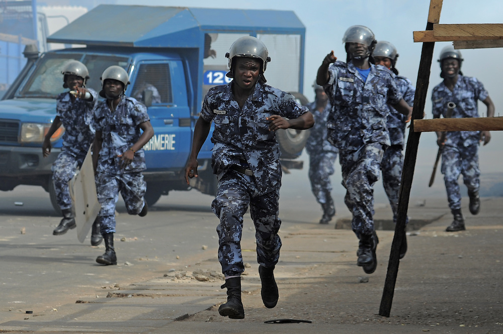 LOME, TOGO - 12-10-05   - Gendarmes run to arrest a man as protesters clash with police in Lomé on October 5. A peaceful protest was scheduled by opposition groups, but their route was blocked by police.  For months, opposition parties have been calling for the departure of president Faure Gnassingbe, whose family has been in power for over 40 years.   Photo by Daniel Hayduk