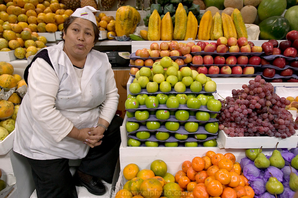A fruit vendor waits for customers in the Santa Carolina Market in Quito, Ecuador. Vendors often sell the same foods as their neighboring competitors. (Supporting image from the project Hungry Planet: What the World Eats.)