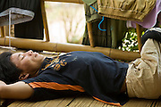 18 FEBRUARY 2008 -- BONG TI, KANCHANABURI, THAILAND: BILAY, a Karen refugee from Burma, relaxes at the Bamboo School in Bong Ti, Thailand, about 40 miles from the provincial capital of Kanchanaburi. Sixty three children, most members of the Karen hilltribe, a persecuted ethnic minority in Burma, live at the school under the care of Catherine Riley-Bryan, whom the locals call MomoCat (Momo is the Karen hilltribe word for mother). She provides housing, food and medical care for the kids and helps them get enrolled in nearby Thai public schools. Her compound is about a half mile from the Thai-Burma border. She also helps nearby Karen refugee villages by digging water wells for them and providing medical care. Bilay, who was stricken by polio when he was a child, said he was forced to do slave labor for the Burmese army before he escaped to Thailand.  Photo by Jack Kurtz