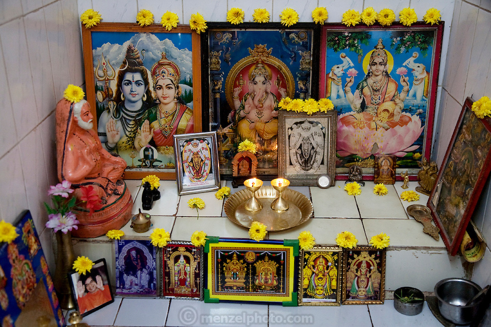 A home shrine in the of house Shashi Kanth, next to their TV. Shashi Kanth is a call center worker who works at an AOL call center in Bangalore, India.  (Shashi Kanth is featured in the book What I Eat: Around the World in 80 Diets.)