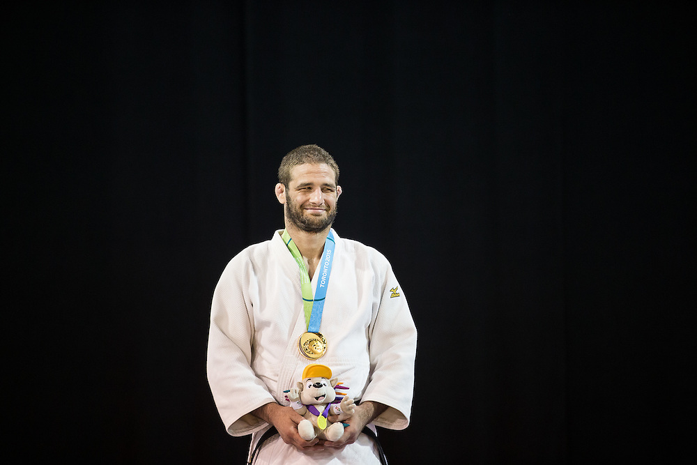 Gold medalist Travis Stevens of the United States smiles as the national anthem is played during the medal ceremony for the men's judo -81kg class at the 2015 Pan American Games in Toronto, Canada, July 13,  2015.  AFP PHOTO/GEOFF ROBINS