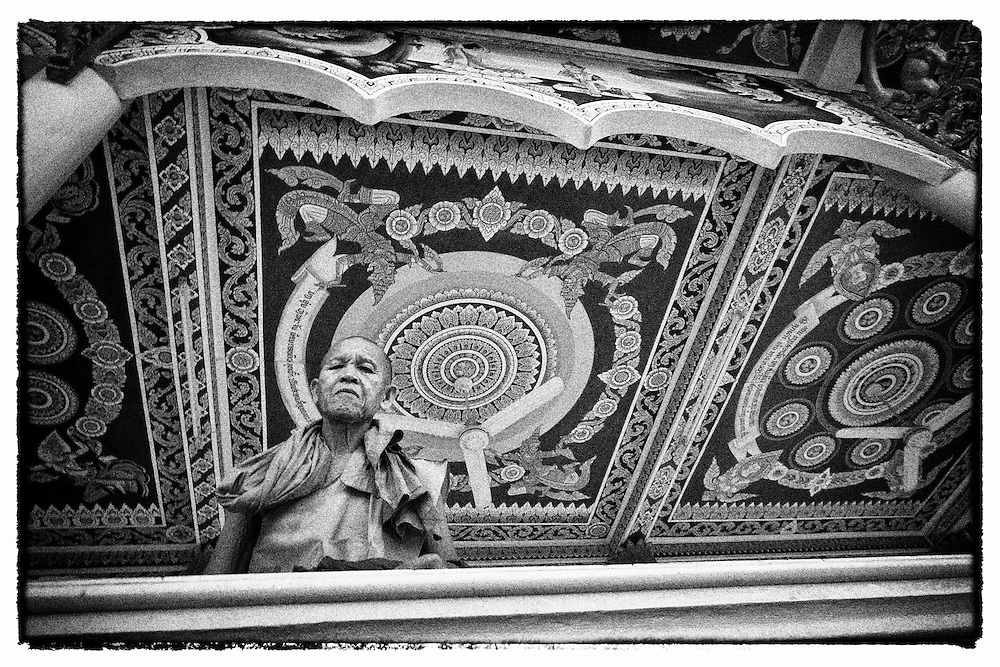 A Buddhist monk looks on from a temple in Vientiane, Laos.