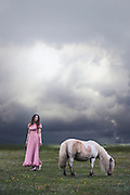 a woman in a pink dress is standing on a paddock with a pony