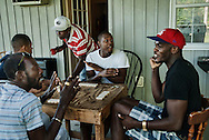 Five men react during a game of dominoes at their residence on the property of a large greenhouse operation. The men are from Jamaica and are participating in a temporary work program. They typically work six days a week for up to eight months per year.