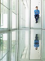 Confident Businessman sitting on desk in office viewed through doorway