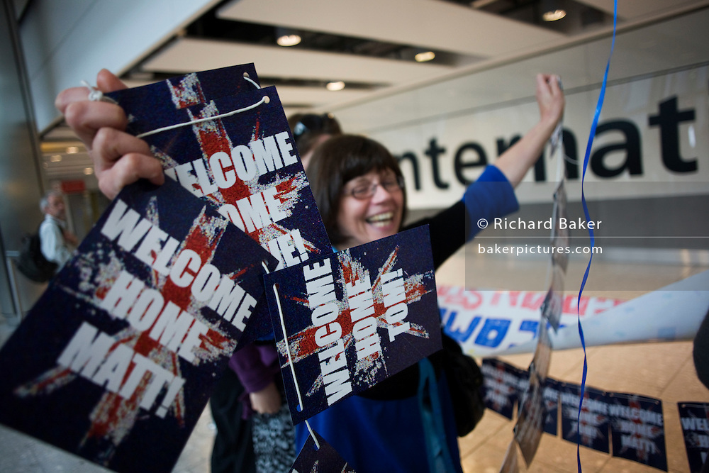 A mother awaitng her son in Arrivals of Heathrow's terminal 5 excitedly waves a Welcome Home Matt banner