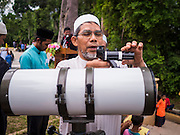 17 JUNE 2015 - YAHA, YALA, THAILAND:  An Imam sets up a telescope used to spot the crescent moon at the Hilal in Yaha. Thousands of people came to Yaha District in Yala province of Thailand for the Hilal - the first sighting of the crescent moon that marks the official beginning of the Muslim holy month of Ramadan. Despite cloudy weather and intermittent rain showers, the moon was sighted and religious leaders declared the official beginning of Ramadan.   PHOTO BY JACK KURTZ