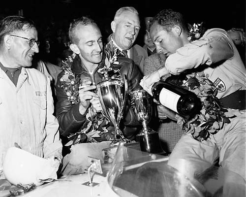 Winners celebrate at 1954 Sebring 12 hour race; at right, Stirling Moss pours the bubbly for his co-driver Bill Lloyd, while their Cunningham team chief mechanic Alfred Momo looks on happily at far left. Background people not known to us. PHOTO BY Ozzie Lyons 1954 / www.petelyons.com