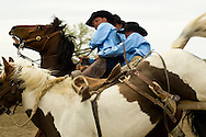 Pick up men Lynn Ashley and Kyle Shaw pick up Saddle Bronc rider Luke Wilson, Miles City Bucking Horse Sale, Montana, <br />