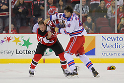 Sep 16, 2013; Newark, NJ, USA; New York Rangers center Brandon Mashinter (40) throws a right hand to the head of New Jersey Devils right wing Cam Janssen (45) during the second period at Prudential Center.
