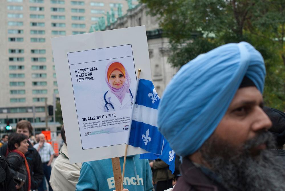 Montr&eacute;al, Canada, le 14 septembre 2013. Des membres de la communaut&eacute; Sikh se joignent &agrave; la manifestation pour protester contre la Charte des valeurs qu&eacute;b&eacute;coises qui interdit aux employ&eacute;s de la fonction publique le port de signes religieux ostensatoires comme le hijab ou la Kippa.<br /> Un h&ocirc;pital ontarien diffuse &agrave; Montr&eacute;al une publicit&eacute; destine aux professionnels de la sant&eacute;. L&rsquo;affiche montre une travailleuse de la sant&eacute; qui porte le hijab. On y lit: &laquo;On ne soucie pas de ce que vous avez sur la t&ecirc;te, mais de ce que vous avez dans la t&ecirc;te&raquo;<br /> Members of the Montreal Sikh Community protesting against the Parti Quebecois proposed Charter of Value. Sikhs working in the public sector would not be allowed to wear their turbans.