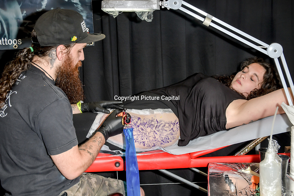 Beards Ink, tattoo a client at The Great British Tattoo Show, on 26 May 2019, London, UK.
