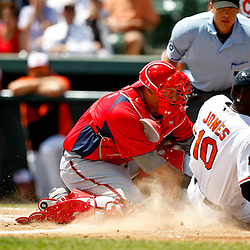 March 24, 2012; Sarasota, FL, USA; Baltimore Orioles center fielder Adam Jones (10) is tagged out at home plate by Washington Nationals catcher Wilson Ramos (3) during the bottom of the first inning of a spring training game at Ed Smith Stadium.  Mandatory Credit: Derick E. Hingle-US PRESSWIRE