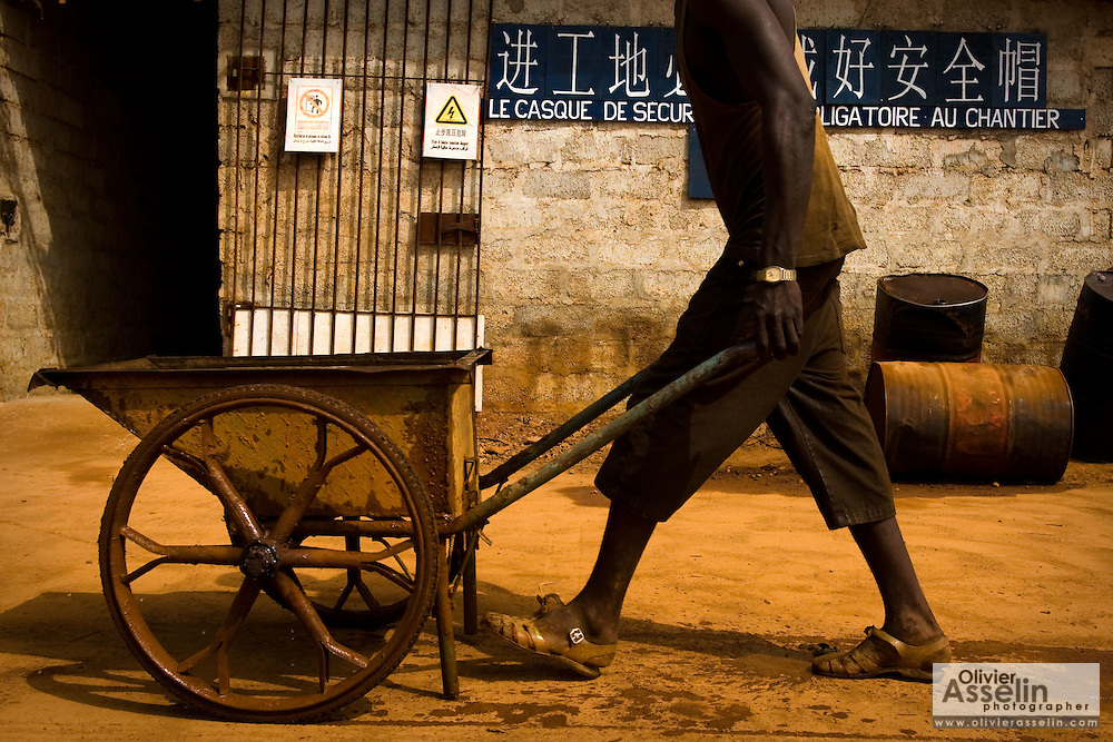 A Guinean worker pushes a wheelcart past a sign written in both chinese and french on the construction site of a new 50,000-seat sports stadium in Conakry, Guinea on Friday March 6, 2009.  The project, an investment of about USD 50 million, is a gift to Guinea from the Chinese government.(Olivier Asselin for the New York Times).